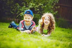 Little girl and boy lying on the green grass and smiling. Royalty Free Stock Photos