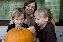 Little girl and boy making a pumpkin lantern with their mother. Royalty Free Stock Images