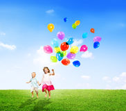 Little Girl and Boy Outdoors Holding Balloons Royalty Free Stock Photos