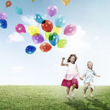 Little Girl and Boy Outdoors Holding Balloons Concept Stock Images