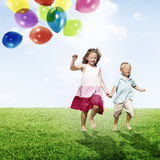 Little Girl and Boy Outdoors Holding Balloons Concept Stock Image