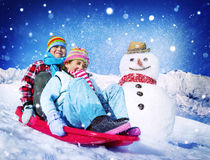 Little Girl and Boy Outdoors Sleding and Snowman Royalty Free Stock Photography