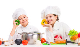 Little girl and boy with pan and ingredients for soup. Little smiling girl and boy with pan and ingredients for soup on kitchen table Stock Images