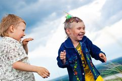 A little girl and boy play and cheered outdoors Royalty Free Stock Photos