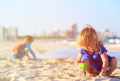 Little girl and boy play with sand on sunset beach Royalty Free Stock Images