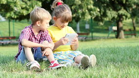 Little girl and boy play with tablet stock video footage