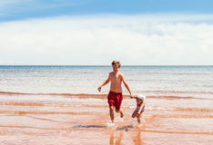 Little girl and boy playing on the beach Stock Photo