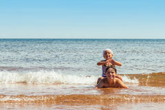 Little girl and boy playing on the beach Stock Photos