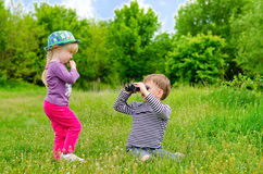 Little girl and boy playing with binoculars Stock Photo