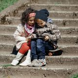 Little girl and boy playing outdoor. Little modern boy and cute girl plaing on the street Royalty Free Stock Photos