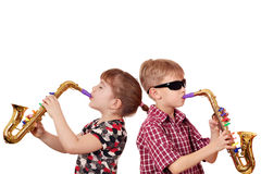 Little girl and boy playing saxophone Stock Images