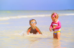 Little girl and boy playing with starfish at beach Royalty Free Stock Photography
