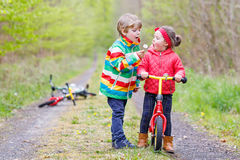 Little girl and boy playing together in forest Stock Images