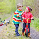 Little girl and boy playing together in forest Stock Photo