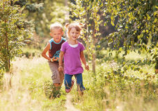 Little girl and boy playing together in sunny summer garden Royalty Free Stock Photos