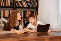 Little girl and boy reading the book stock image