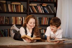 Little girl and boy reading the book stock photography