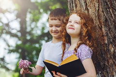 Little girl and boy reading book in the park. Stock Photos