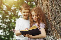 Little girl and boy reading book in the park. Royalty Free Stock Photography