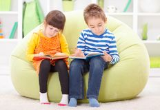 Little girl and boy reading stock photo