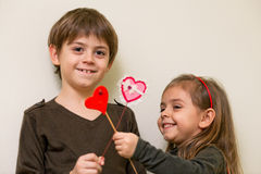 Little girl and boy with red hearts. Boy gives heart to little girl  and little girl  gives heart to boy Stock Photo