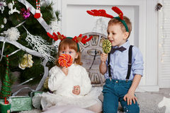 Little girl and boy in reindeer antlers eating a lollipops Royalty Free Stock Photos