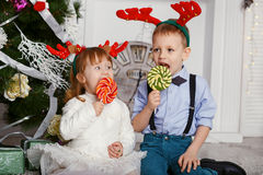 Little girl and boy in reindeer antlers eating a lollipops. Stock Photography
