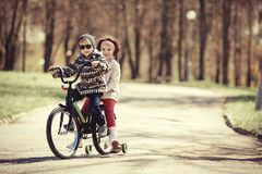 Little girl and boy riding on bicycle together stock photo