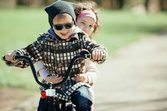 Little girl and boy riding on bicycle together Stock Image