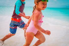 Little girl and boy run play with waves on beach. Vacation stock photography