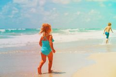 Little girl and boy run play with waves on beach Stock Photos