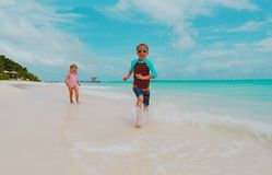 Little girl and boy run play with waves on beach. Vacation royalty free stock images