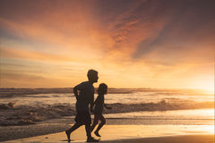 Little girl and boy running on beach stock photo