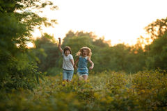 Little girl and boy are running in forest and holding hands. Royalty Free Stock Image