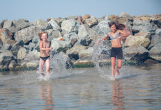 Little girl and boy in the sea Stock Images