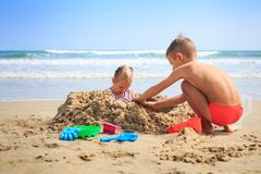 Little Girl Boy Sit near Heap Play at Wave Surf on Beach. Little blond girl sits in sand hole boy squats near heap and play with toys on beach against wave surf Royalty Free Stock Photo