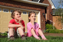 Little girl and boy sits on grass near cottage Royalty Free Stock Photo