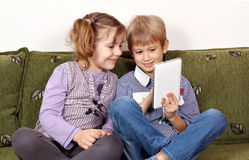 Little girl and boy play with tablet Stock Image