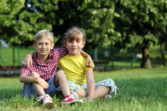 Little girl and boy sitting on grass Stock Photography