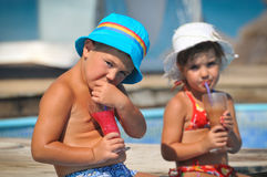 Little girl and boy sitting in the pool and drink Royalty Free Stock Photography