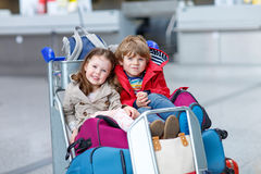 Little girl and boy sitting on suitcases on airport. Two adorable little siblings, kid boy and girl sitting on suitcases on international airport. Brother and Royalty Free Stock Photos