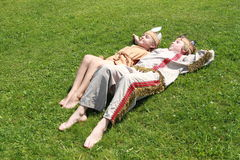 Little girl and boy sleaping on grass. Barefoot little girl and boy in indian dress sleaping on grass Stock Photo
