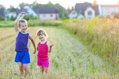 Little girl and boy standind on field with golden sunlight Stock Images