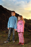 Little girl and boy standing near hill Stock Photography