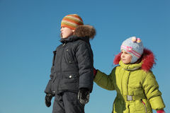 Little girl and boy standing at snow Stock Photos