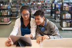 Cheerful kids watching tablet in library stock photography