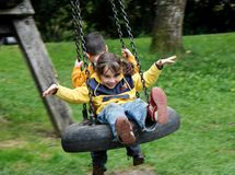 Little girl and boy swing Stock Photos