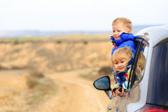 Little girl and boy travel by car in mountains Stock Photography