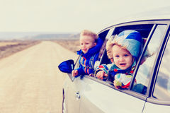 Little girl and boy travel by car on the road Royalty Free Stock Images