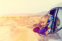 Little girl and boy travel by car on the road Stock Image